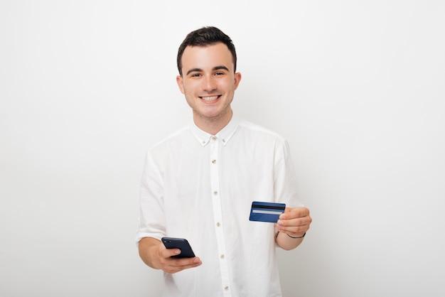 Uśmiechnięty młody człowiek patrzeje kamerę i trzyma jego kredytową kartę w bielu na bielu. bankowość mobilna i zakupy online.
