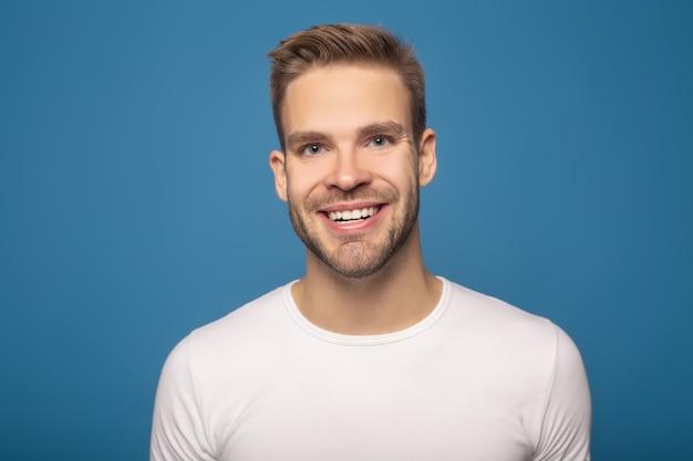 Uśmiechnięty młody człowiek patrzeje kamerę odizolowywającą na błękicie