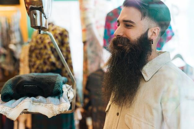 Uśmiechnięty młody człowiek patrzeje skale w odzieżowym sklepie