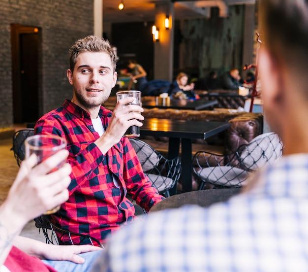 Uśmiechnięty młody człowiek pije piwo z przyjaciółmi w pubie
