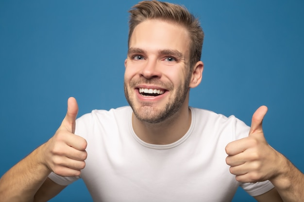 Uśmiechnięty młody człowiek pokazuje aprobaty odizolowywać na błękicie