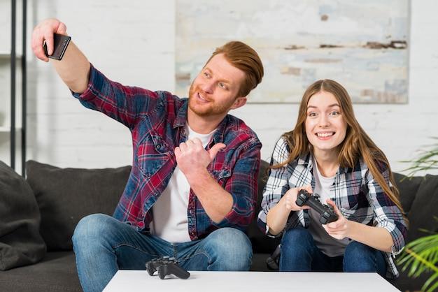 Uśmiechnięty młody człowiek pokazuje kciuk up podpisuje podczas gdy brać selfie na telefonie komórkowym w domu