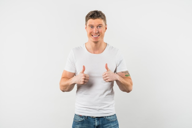 Uśmiechnięty młody człowiek pokazuje kciuk up z dwa rękami przeciw białemu tłu