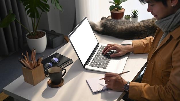 Uśmiechnięty młody człowiek pracujący online z komputerem laptop w komfortowym domu.
