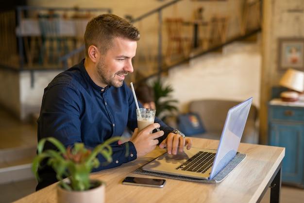 Uśmiechnięty młody człowiek pracuje na komputerze w przytulnej restauracji cafe bar
