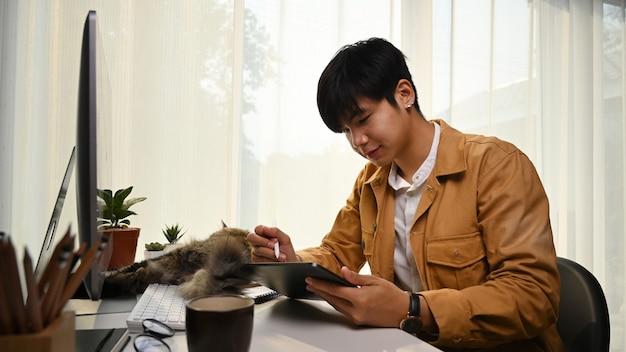 Uśmiechnięty młody człowiek projektant za pomocą cyfrowego tabletu siedząc w wygodnym biurze domowym.