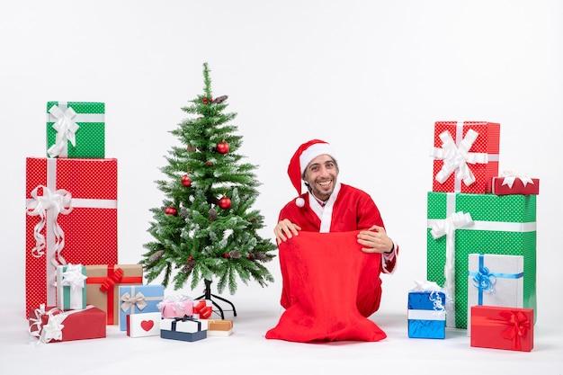 Uśmiechnięty młody człowiek przebrany za świętego mikołaja z prezentami i zdobioną choinką siedzi na ziemi pozuje do aparatu na białym tle