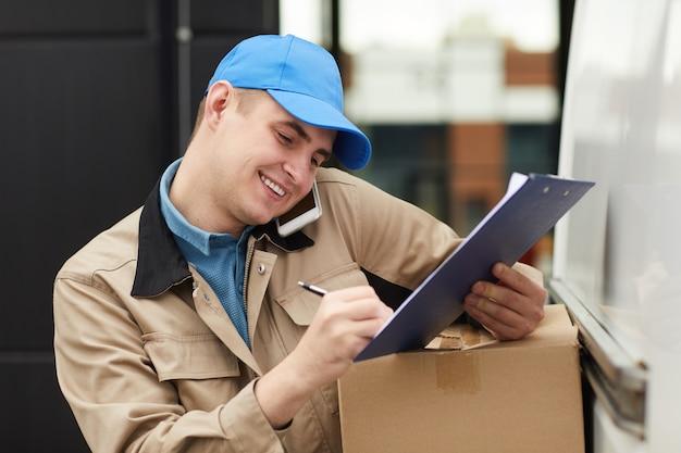 Uśmiechnięty młody człowiek przyjmuje zamówienie przez telefon i realizuje dostawę