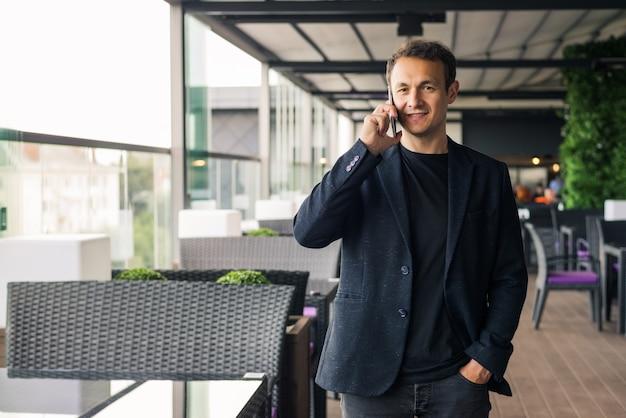 Uśmiechnięty młody człowiek rozmawia przez telefon komórkowy w kawiarni