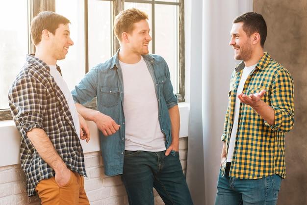 Uśmiechnięty młody człowiek rozmawia z przyjaciółmi w pobliżu okna