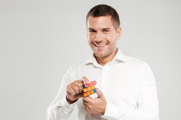 Uśmiechnięty młody człowiek rozwiązuje kostkę rubika.