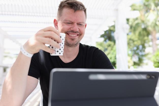 Uśmiechnięty młody człowiek siedzący z filiżanką kawy i pracujący na tablecie na ulicy
