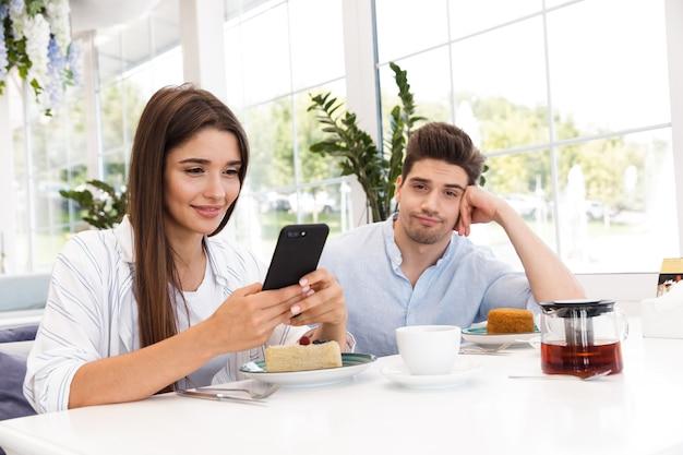 Uśmiechnięty młody człowiek siedzi przy stoliku w kawiarni, podczas gdy jego dziewczyna za pomocą telefonu komórkowego