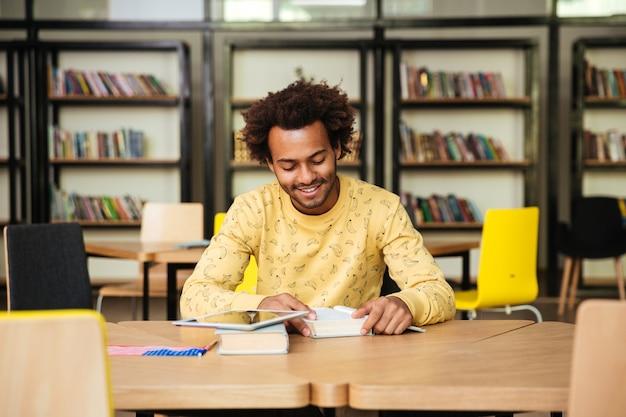 Uśmiechnięty młody człowiek siedzi w bibliotece i czyta