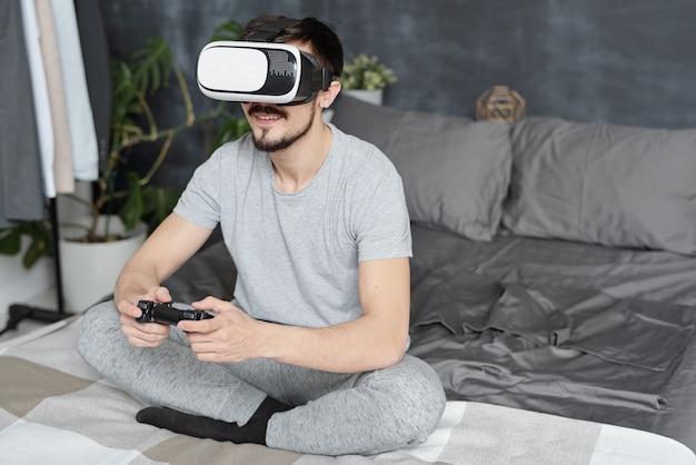 Uśmiechnięty młody człowiek siedzi ze skrzyżowanymi nogami na łóżku i grając w gry wideo za pomocą joysticka i zestawu słuchawkowego wirtualnej rzeczywistości