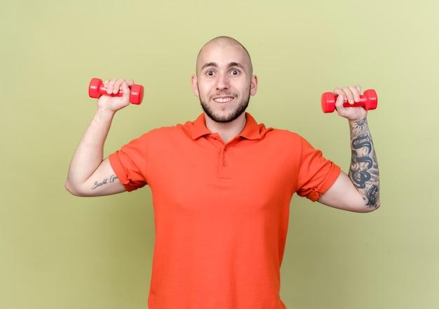 Uśmiechnięty młody człowiek sportowy ćwiczenia z hantlami na białym tle na oliwkowej ścianie