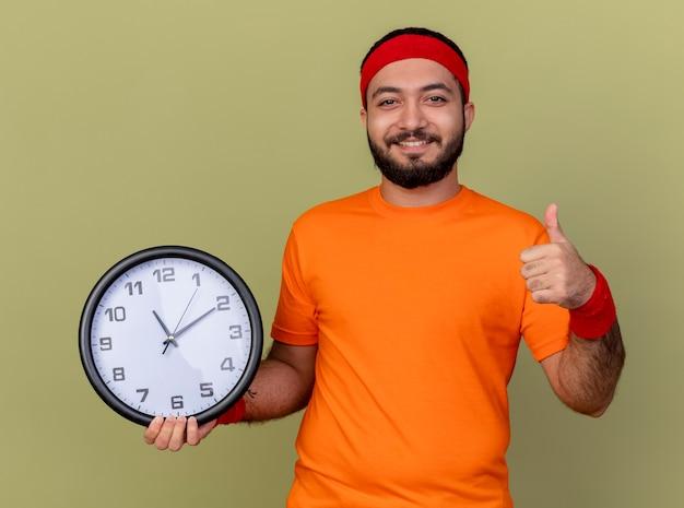 Uśmiechnięty młody człowiek sportowy na sobie opaskę i opaskę trzymając ścianę