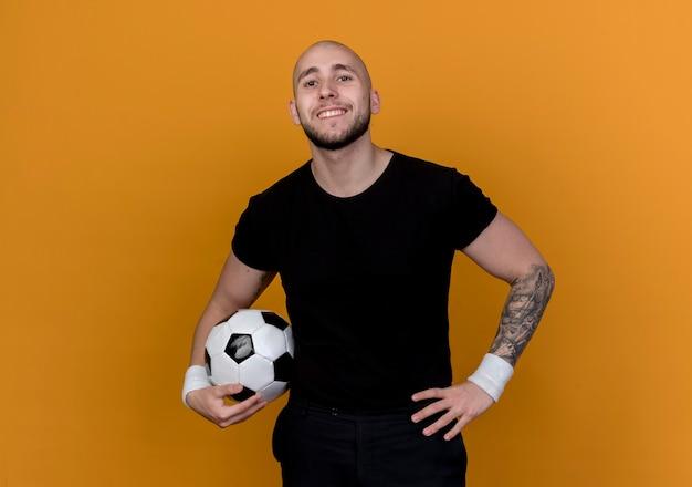 Uśmiechnięty młody człowiek sportowy na sobie opaskę na nadgarstek, trzymając piłkę i kładąc rękę na biodrze na białym tle na pomarańczowej ścianie
