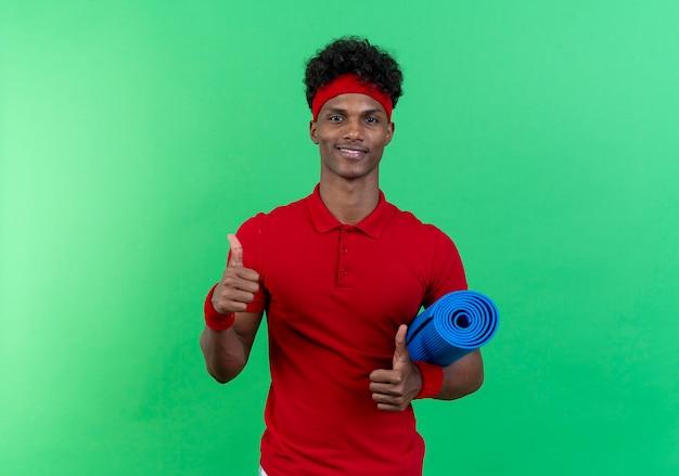 Uśmiechnięty młody człowiek sportowy noszenia opaski i nadgarstka trzymając matę do jogi
