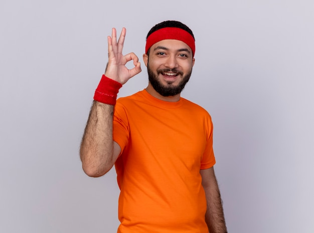 Uśmiechnięty młody człowiek sportowy noszenia opaski i opaski na rękę pokazując dobry gest na białym tle