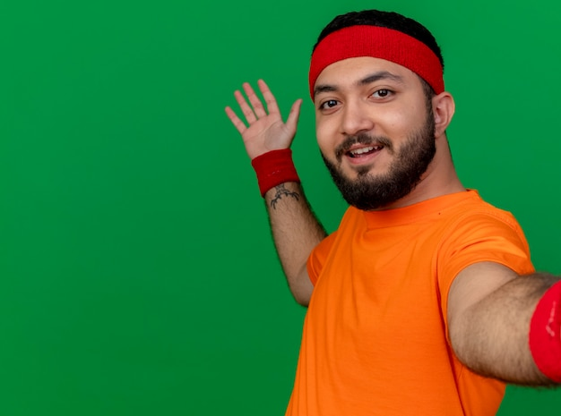 Uśmiechnięty młody człowiek sportowy noszenia opaski i opaski na rękę trzymając punkty aparatu