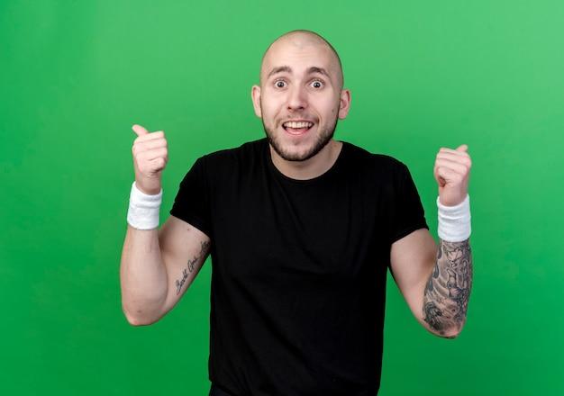 Uśmiechnięty Młody Człowiek Sportowy Noszenia Opaski Kciuki Do Góry Na Białym Tle Na Zielono Darmowe Zdjęcia