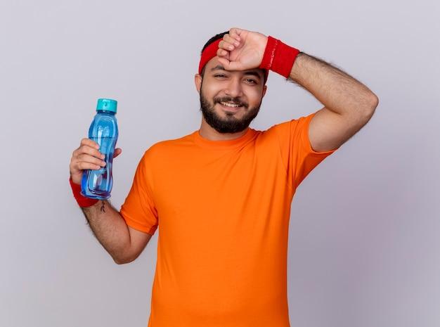 Uśmiechnięty młody człowiek sportowy noszenia opaski na głowę i opaski, trzymając butelkę wody i wycierając czoło ręką na białym tle