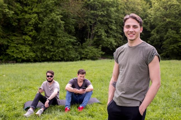 Uśmiechnięty młody człowiek stoi na polu z przyjaciółmi