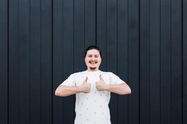 Uśmiechnięty młody człowiek stoi przeciw czarnemu tłu pokazuje kciuk up podpisuje z dwa palcami