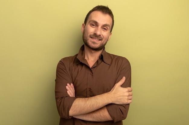 Uśmiechnięty młody człowiek stojący z zamkniętą postawą patrząc z przodu na białym tle na oliwkowej ścianie