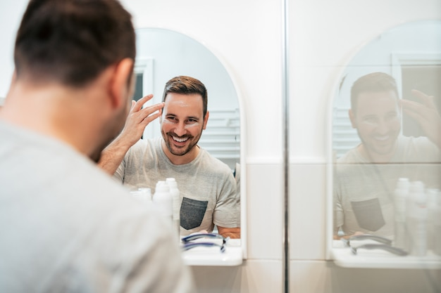 Uśmiechnięty młody człowiek stosuje creme w łazience.