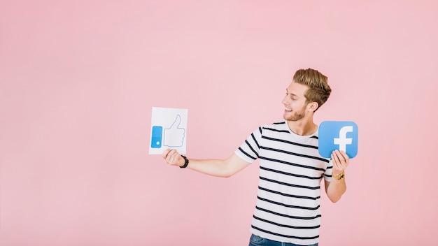 Uśmiechnięty młody człowiek trzyma jak i facebook ikona