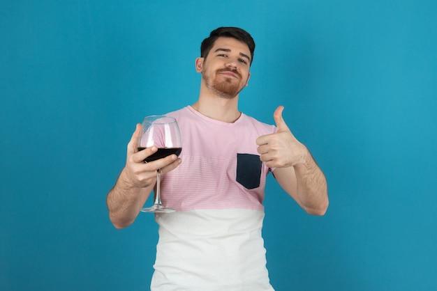 Uśmiechnięty młody człowiek trzyma kieliszek wina i wskazując kciuk w górę.