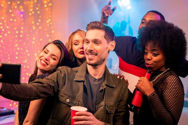 Uśmiechnięty młody człowiek trzyma smartfon przed sobą, robiąc selfie z międzykulturowymi przyjaciółmi i pijąc drinki na imprezie