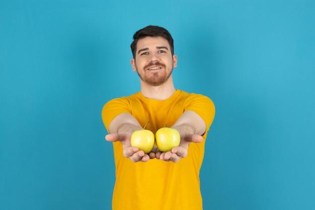 Uśmiechnięty młody człowiek trzyma świeże jabłka i pokazuje do kamery.