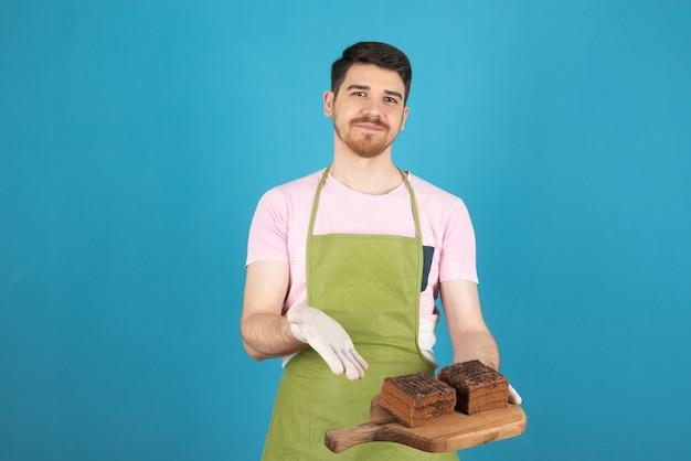 Uśmiechnięty młody człowiek trzyma świeże plastry ciasta i wskazując na to rękę.