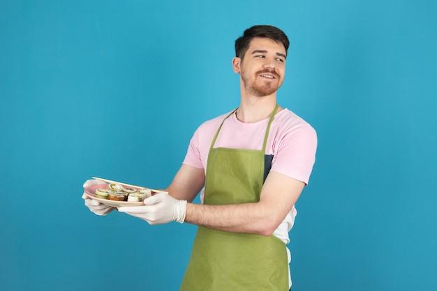 Uśmiechnięty młody człowiek trzyma świeże plastry ciasta.