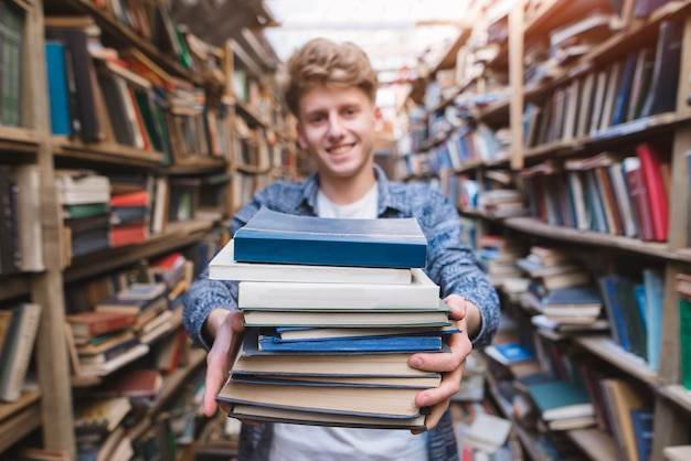 Uśmiechnięty młody człowiek trzyma wiele książek w jego rękach