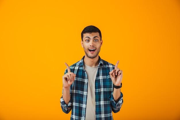 Uśmiechnięty młody człowiek ubrany w kratę koszulę stojącą na białym tle nad pomarańczową ścianą, skierowaną w górę