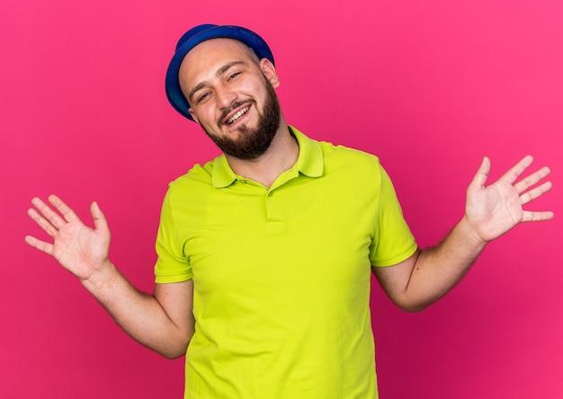 Uśmiechnięty młody człowiek ubrany w niebieski kapelusz imprezowy rozkładający ręce na różowej ścianie