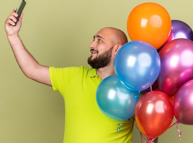 Uśmiechnięty młody człowiek ubrany w żółtą koszulkę trzymający balony robi selfie na oliwkowo-zielonej ścianie