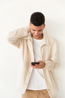 Uśmiechnięty młody człowiek używa telefon komórkowego