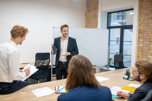 Uśmiechnięty młody człowiek w garniturze stojący na stojaku pokazując smartfon i siedzący zainteresowani koledzy