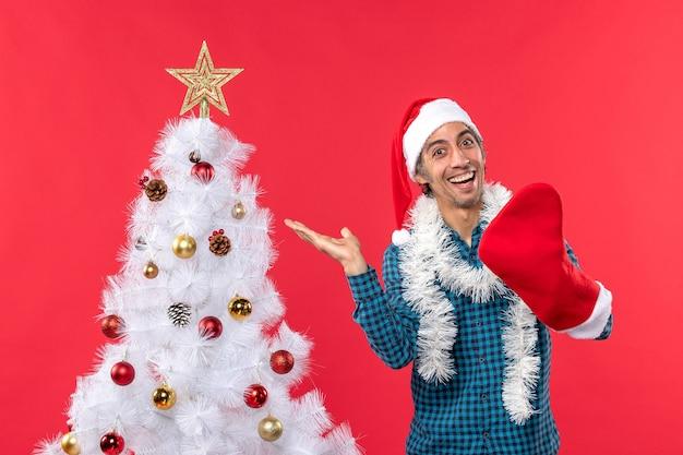 Uśmiechnięty młody człowiek w kapeluszu świętego mikołaja w niebieskiej koszuli w paski i noszący swoją świąteczną skarpetę w pobliżu choinki na czerwonym materiale