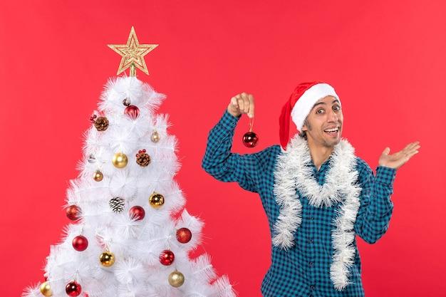 Uśmiechnięty młody człowiek w kapeluszu świętego mikołaja w niebieskiej koszuli w paski i trzymając dodatek do dekoracji