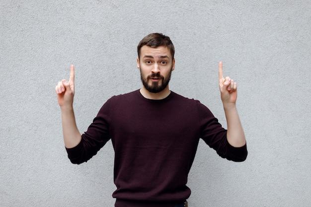 Uśmiechnięty młody człowiek w niebieskiej eleganckiej odzieży casual, pokazujący się na czymś lub kopiujący miejsce na tekst lub hasło, wykonujący gest ręką znak pomysłu, na szarym tle. emocje i koncepcja sukcesu.