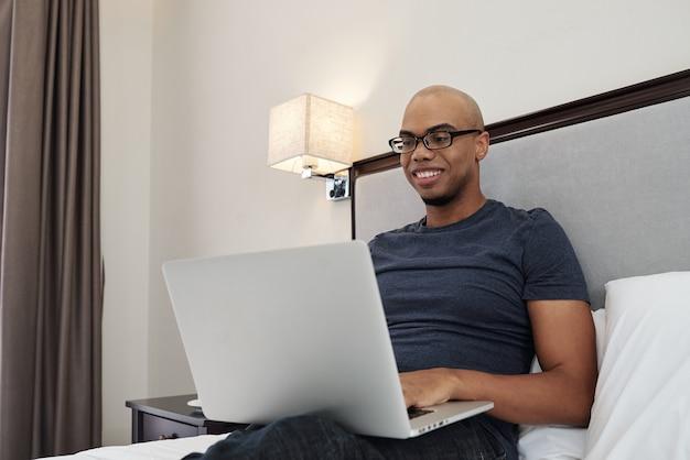 Uśmiechnięty młody człowiek w okularach siedzi na łóżku i programowanie na laptopie