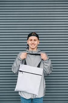 Uśmiechnięty młody człowiek w stylowe ubranie stoi z białą torbą na zakupy w ręce na szaro i patrzy w kamerę z uśmiechem na twarzy