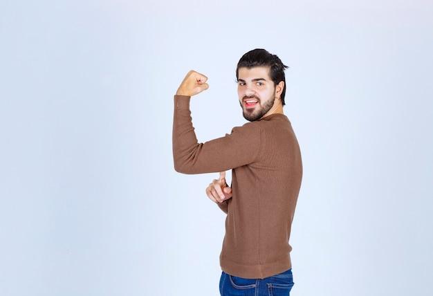 Uśmiechnięty młody człowiek w swetrze pokazuje biceps i patrząc na kamery. zdjęcie wysokiej jakości