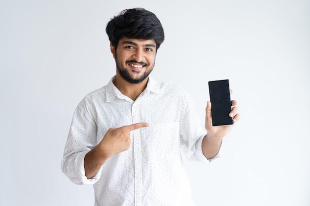 Uśmiechnięty młody człowiek wskazuje przy smartphone i patrzeje kamerę